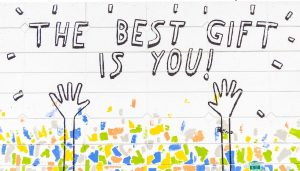 Photograph of graffiti showing hands stretch upwards against a multi-coloured background and the words 'the best gift is you'