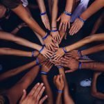 Several people's hands joined together in the centre of a circle