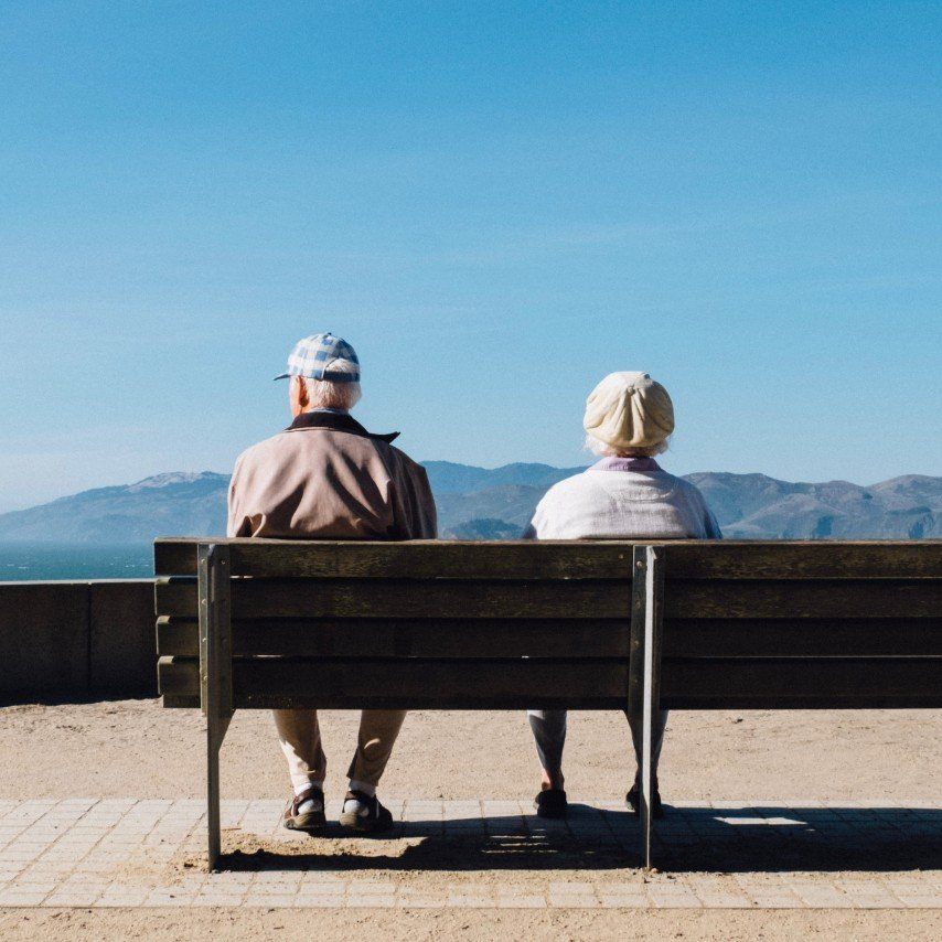 Older couple sitting on a bench looking towards some hills