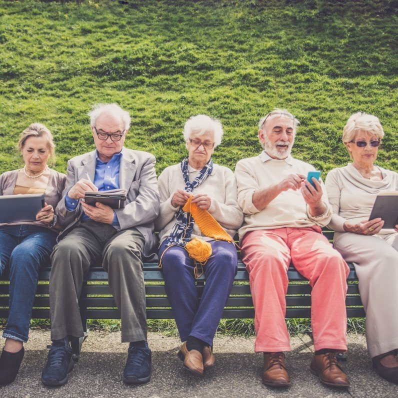 Older people sitting on a bench looking at digital devices, books and knitting