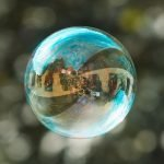 A photography of a bubble with some buildings and people reflected inside.